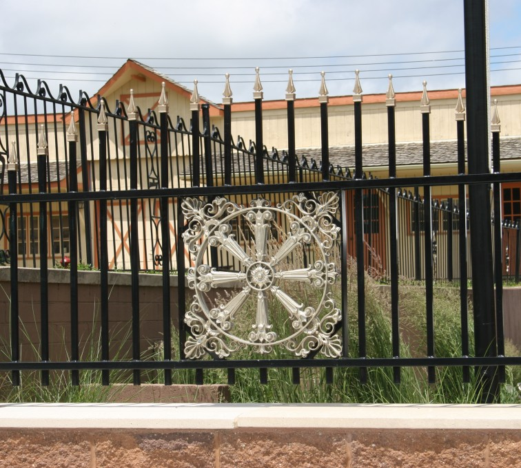 The American Fence Company - Custom Iron Gate Fencing, 1230 Over arch with quad flare & emblem
