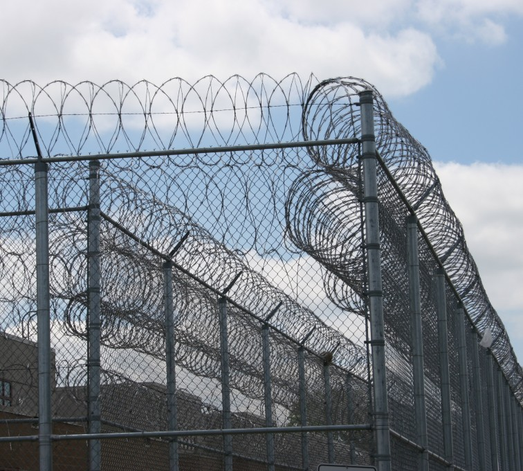 Several lines of tall high security fence with coils of razor wire on top with barb wire strung along barb arms