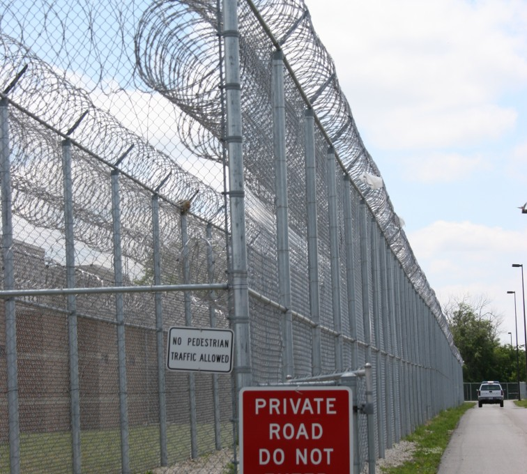 2 layers of high security fence with Concertina wire strung on top. Two signs are attached to the fence, one small white one that reads