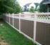 A side of a yard with a vinyl privacy fence, weathered cedar pickets and outlined with white posts, rails and lattice