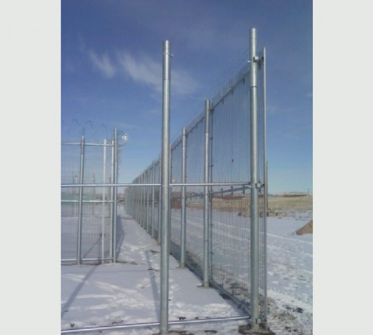 Barely visible anti-climb mesh is strung up between steel posts for a high security fence at a correctional facility