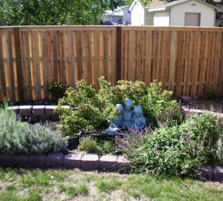 A small garden with a few varieties of flowers with an alternating board custom wood fence stationed a few feet behind it