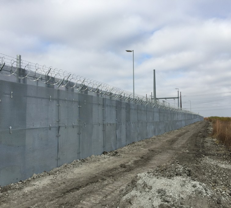 A shot of a long stretch of high security fence with ballistic characteristics. This fencing also has barb wire and razor wire installed on top.
