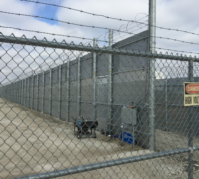 A view of a ballistic high security fence through some chain link mesh