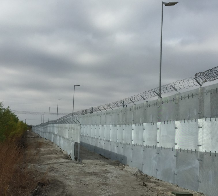Two parallel stretches of ballistic high security fencing. The front section is shorter and has barb wire on time, where as the second stretch is about 1/3 taller and has razorwire and barb wire.