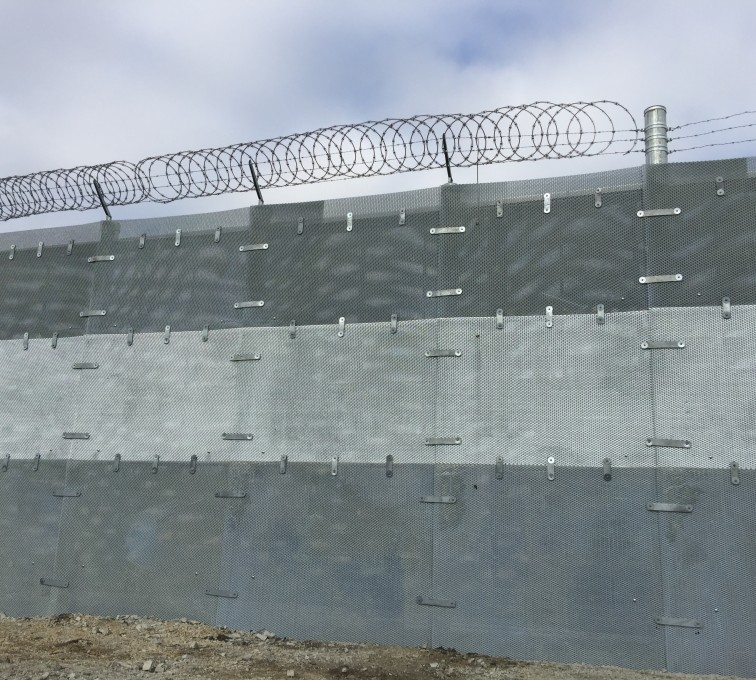 The outside view of a tri-tone ballistic high security fence with razor and barb wire