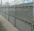 Several sections of high security ballistic fence with barb wire and razor wire installed on top