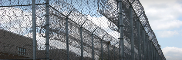 Several sets of high security fence with spirals of barb wire at the top