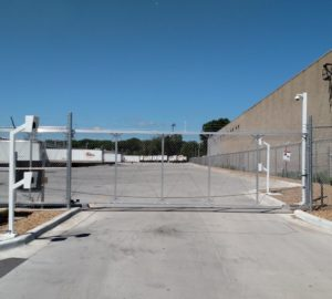 A chain link aluminum cantilever gate in front of an industrial complex