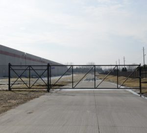A black chain link cantilever gate set on a private road near an industrial building