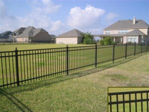 A flat top ornamental iron fence stretched across a backyard with a closeup of the flat top