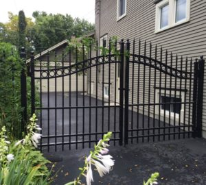 A black ornamental iron overscallop estate gate next to the side of the house