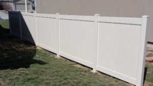 A section of a privacy vinyl fence in a diagonal shot near the side of a house