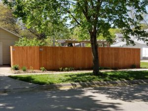 A stained cedar-tone fir picket fence with an American Fence logo plate in the upper left corner