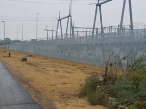 A high security fence with large industrial features laying beyond it