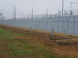 A distance shot of a high security fence with large industrial features laying beyond it