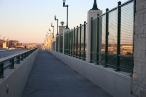 A square mesh panel system fence stretched across the side of a bridge