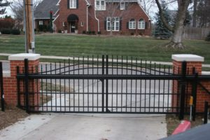 An iron ornamental over arch cantilever gate set on a residential street in front of a residential driveway