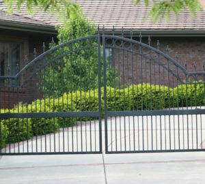 A spear top over arch ornamental swing gate in front of a curving driveway