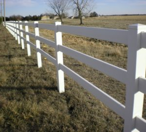 A white vinyl ranch rail stretching off into the distance on a field