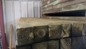 A neatly organized pile of square green treated posts in a warehouse