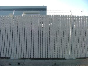 White slats woven through a barb wire chain link fence