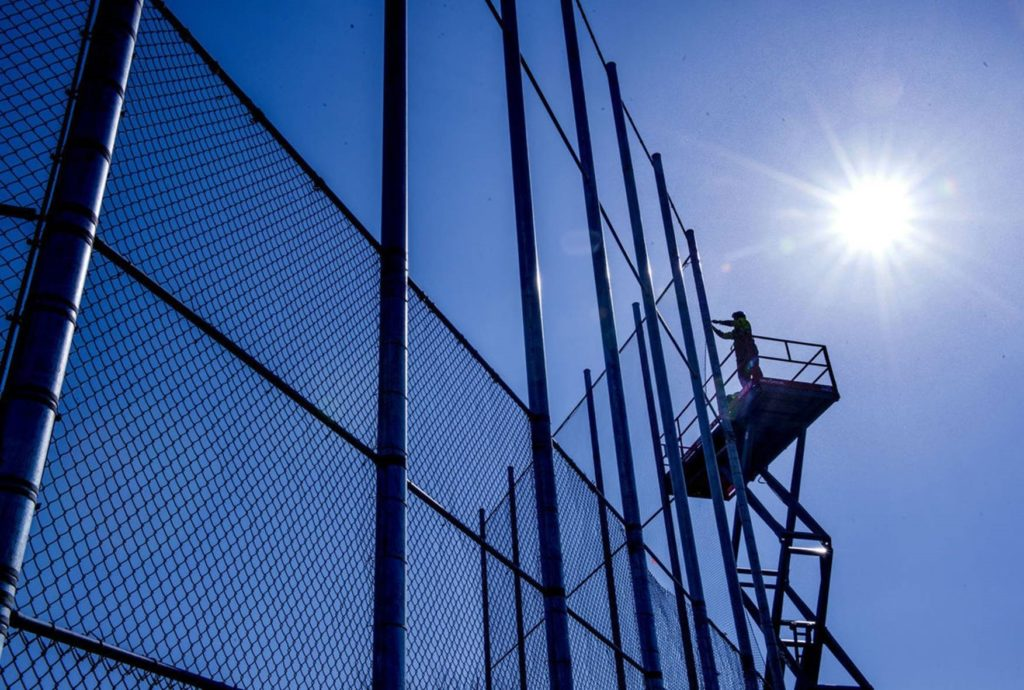 An American Fence Company worker installing chain link fabric on Nebraska Wesleyan University's backstop. He is standing on a lift and has the sun blazing behind him in a cloudless blue sky