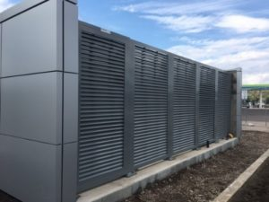 Gunmetal gray horizontal louvered panels securing an outdoor mechanical equipment system