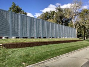A long stretch of louvered screening across a green, grassy plot