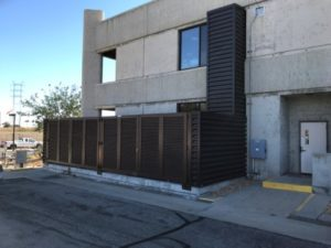 Dark brown horizontal louver screening surrounding the side of a concrete building