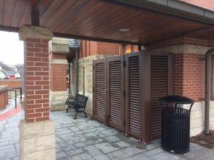 Dark brown horizontal louvered screening keeping mechanical equipment secure