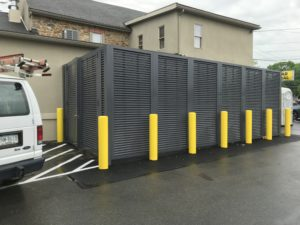 Dark grey PalmSHIELD horizontal louvers installed behind yellow traffic posts in front of Mission Dispensary in Allentown, PA