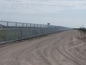 A long row of security chain link fencing installed by American Fence Company at Husker Harvest Days. This chain link fence has top and bottom rail for ultimate security
