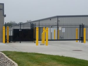 An ornamental iron cantilever gate with a keypad and gate operator surrounded by bright yellow traffic pillars for protection