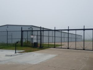 A black vinyl chain link cantilever gate with barb wire installed in front of a large nondescript warehouse. This hate has a manual keypad installed that is wired to an access control operator