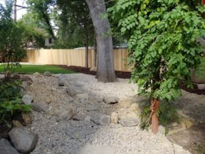 A dry river bed feature installed with large and small stones, greenery and a stone retaining wall