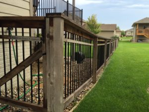 Custom wood fencing with American Fence Company plaque stretching across a large, vibrant green lawn