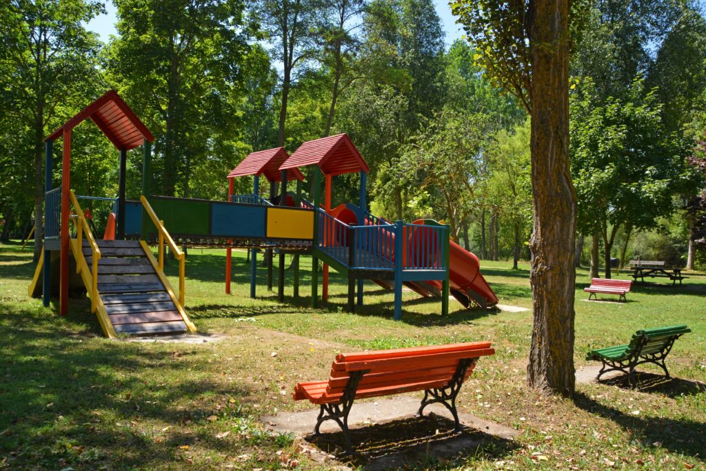 A park bench overlooking a play structure in primary colors