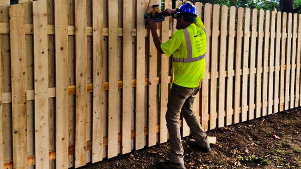 Wood board on board fence installed by the American Fence Company.