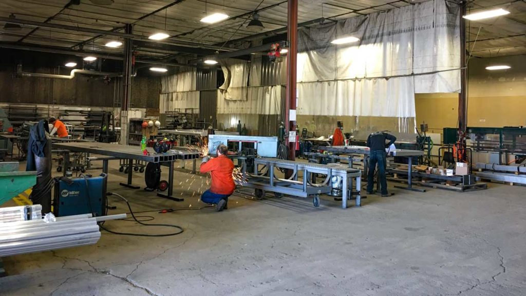 Custom metals shop with workers creating fence materials.